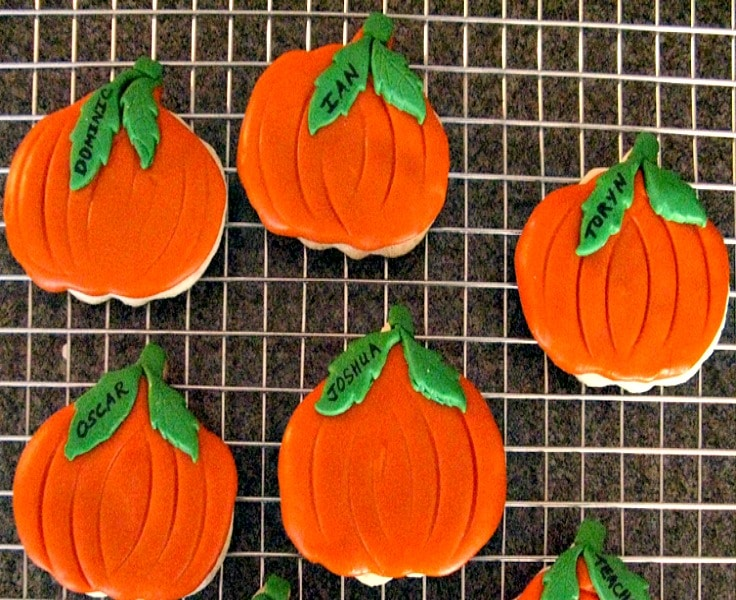 fondant covered orange Halloween pumpkin cookies on wire cooling rack