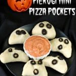 pierogi mini pizza pockets on a black plate with a pumpkin in the background