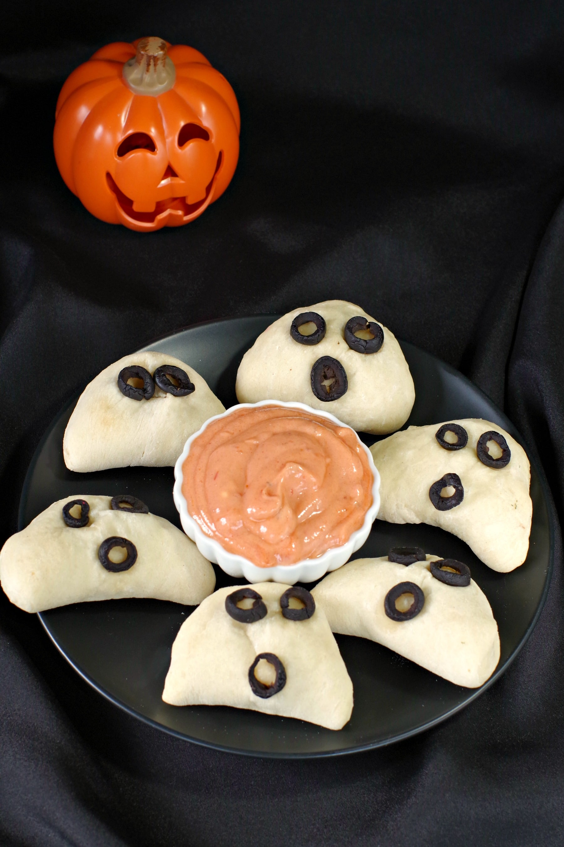 halloween pizza pockets on a black plate with dip in the middle and plastic jack o'latern in the background