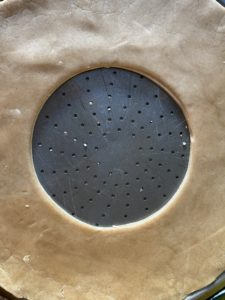 pizza pan with gingerbread dough and hole cut out of the middle
