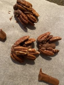pecan chocolate pine cones being made on parchment paper