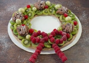 Edible Christmas Wreath made of gingerbread, fruits and nuts on a brown wooden surface