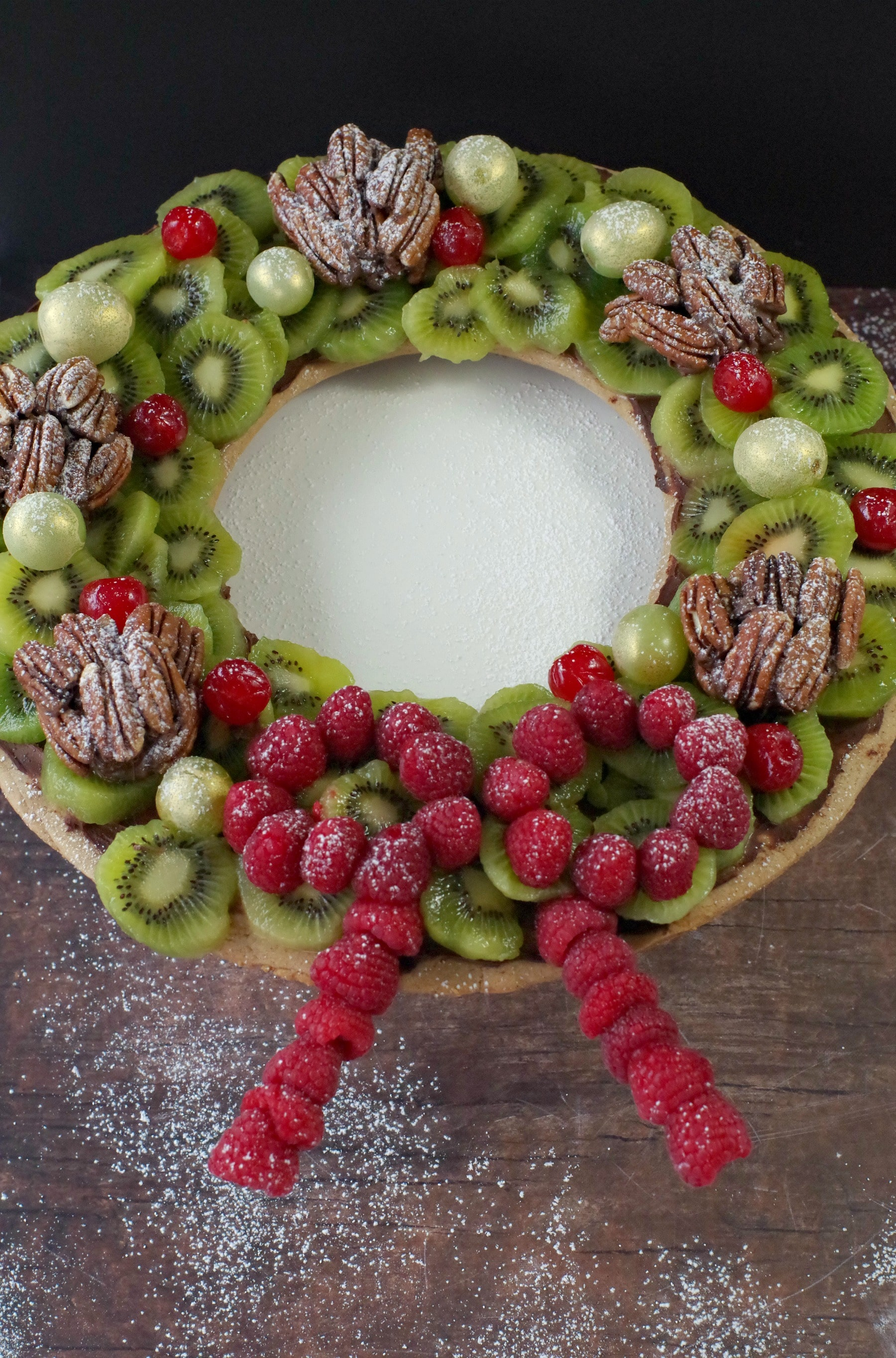 Gingerbread Edible Christmas Wreath with fruit and nuts, on brown wooden surface with powdered sugar sprinkles