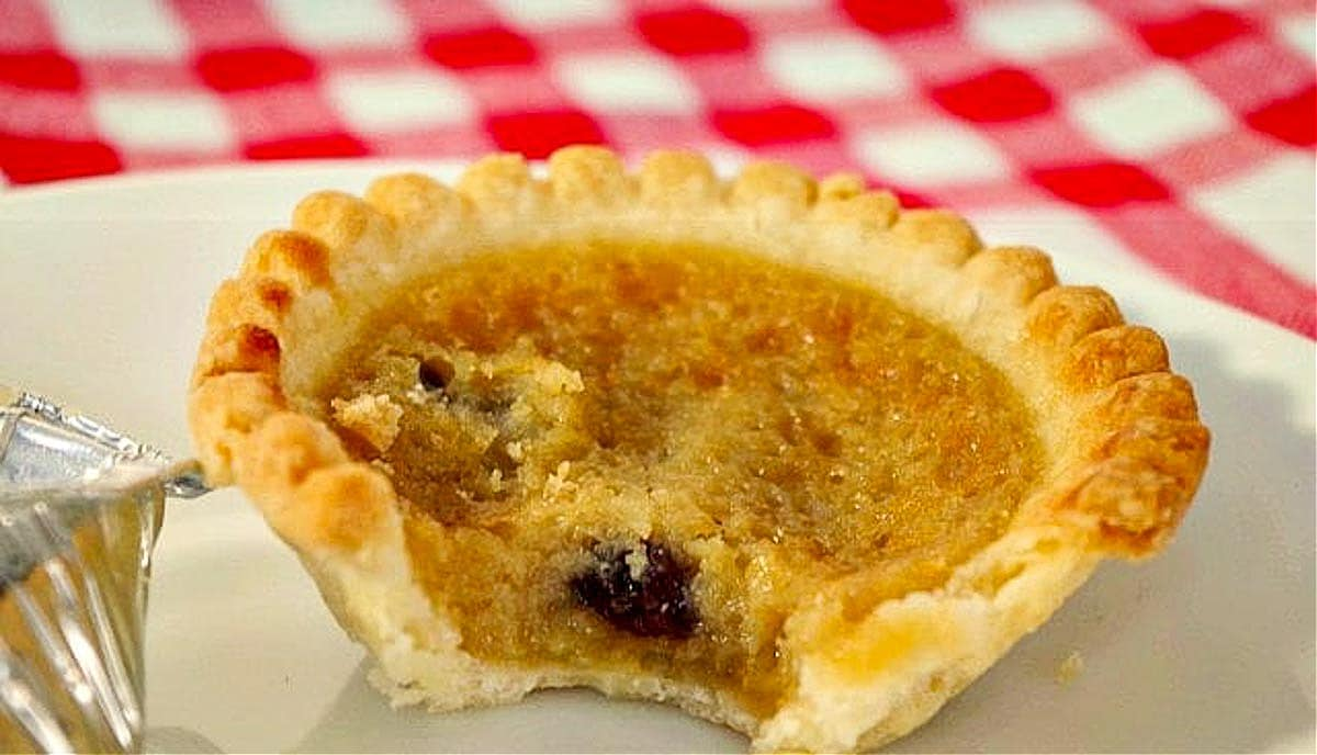 butter tart with bite taken out, on a white plate on red checkered tablecloth