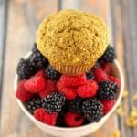 bran muffin sitting on a bowl of berries