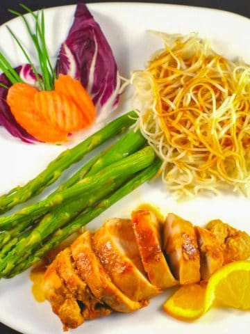 Hoisin sauce with chicken on white plate with asparagus and chow mein noodles