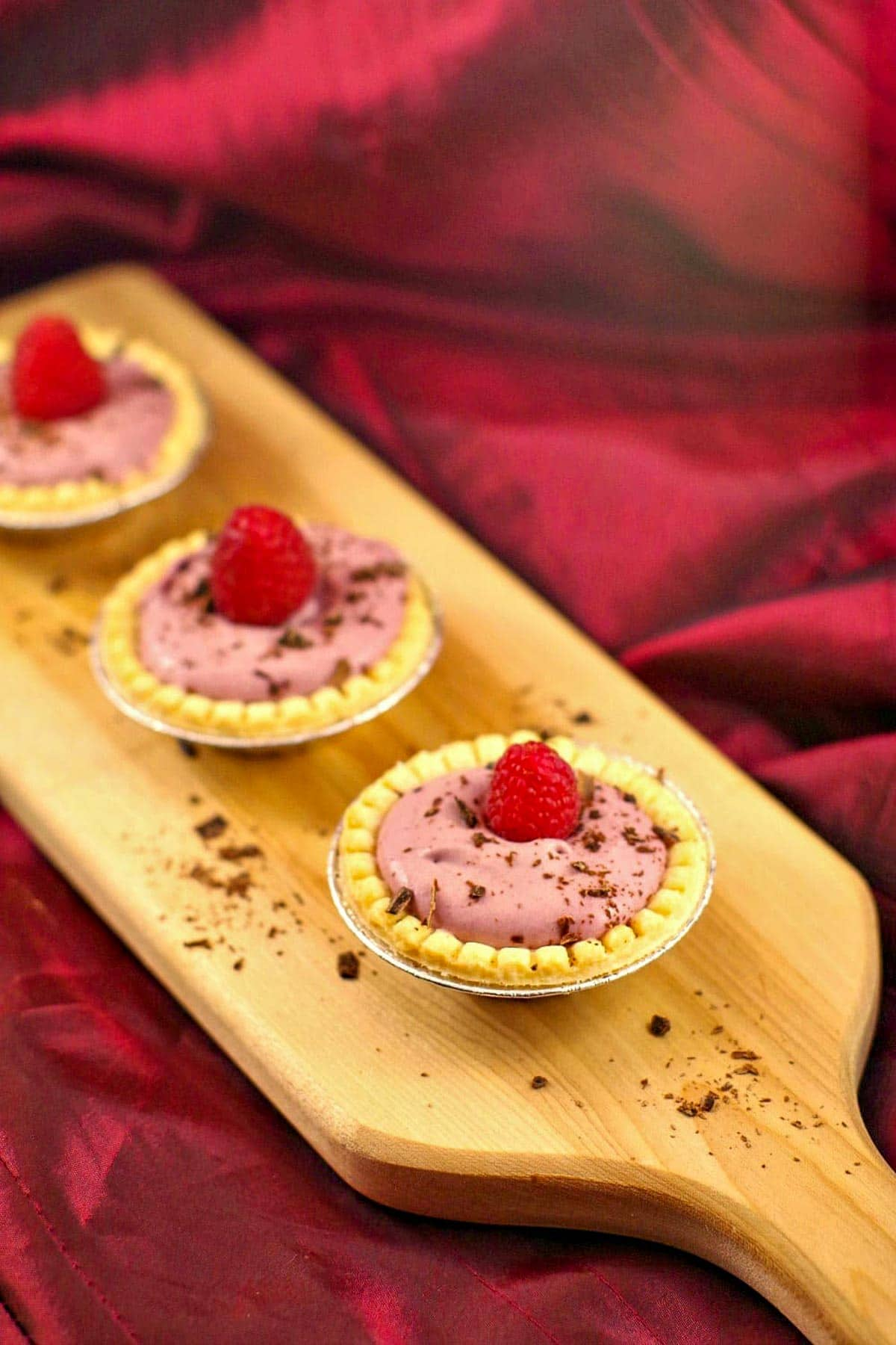 3 raspberry tiramisu tarts on a narrow wooden cutting board