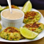 Canned salmon patties on white plate, with dip in the middle and lime wedges