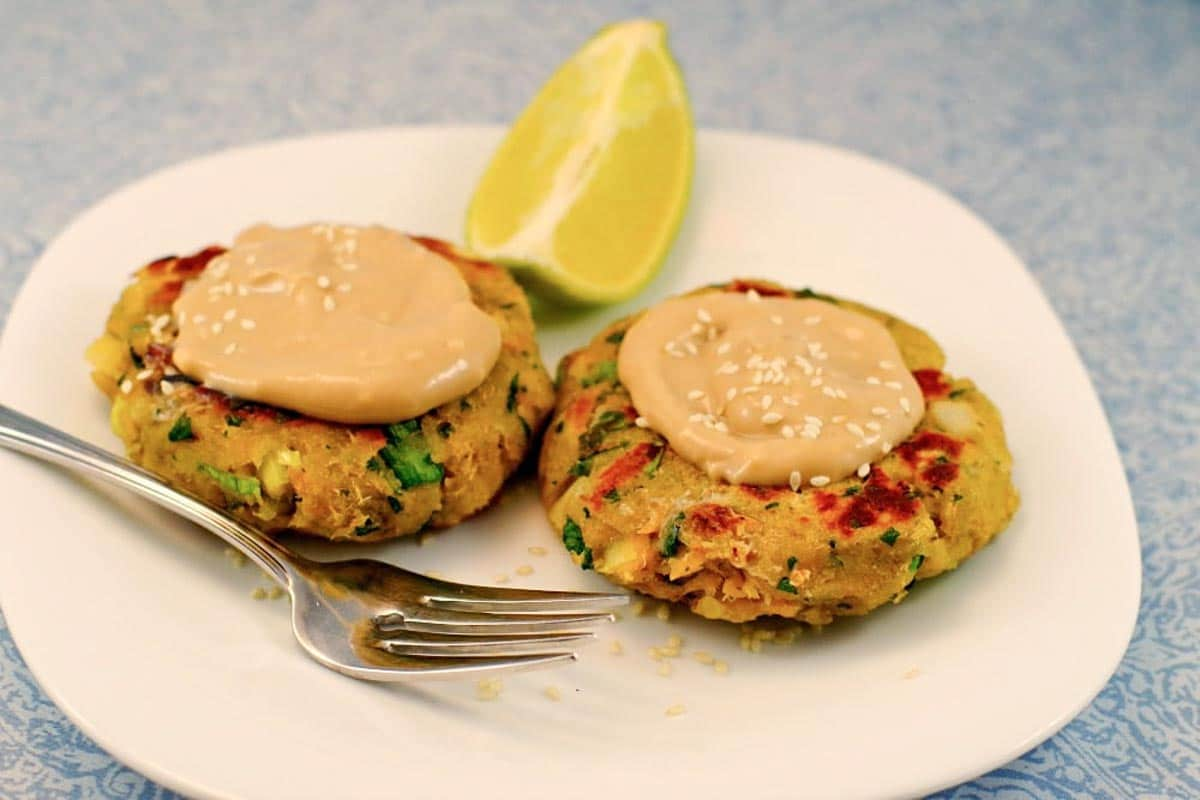 2 canned salmon patties on a white plate, with a fork and wedge of lime