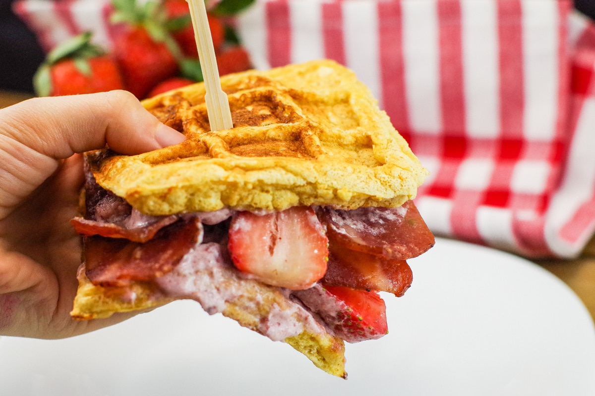 chicken and waffle sandwich being held up in a hand with strawberries in background
