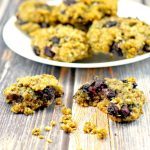 Saskatoon berries cookie broken in half with a plate of Juneberry cookies in the background