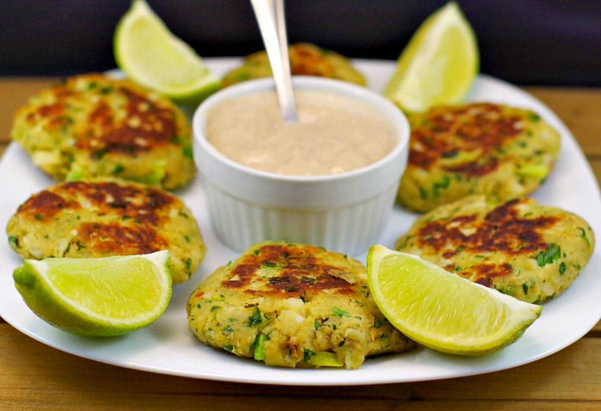 Pan-fried salmon patties on white plate, with dip in the middle and lime wedges