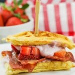 chicken and waffle sandwich with strawberries in background