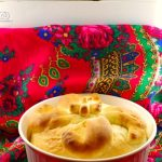Paska in a white casserole dish on red patterned cloth with bread machine in the background