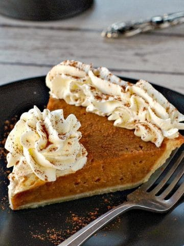 piece of pumpkin pie with whipped cream on a black plate with black platter stand in the background, with pie on platter
