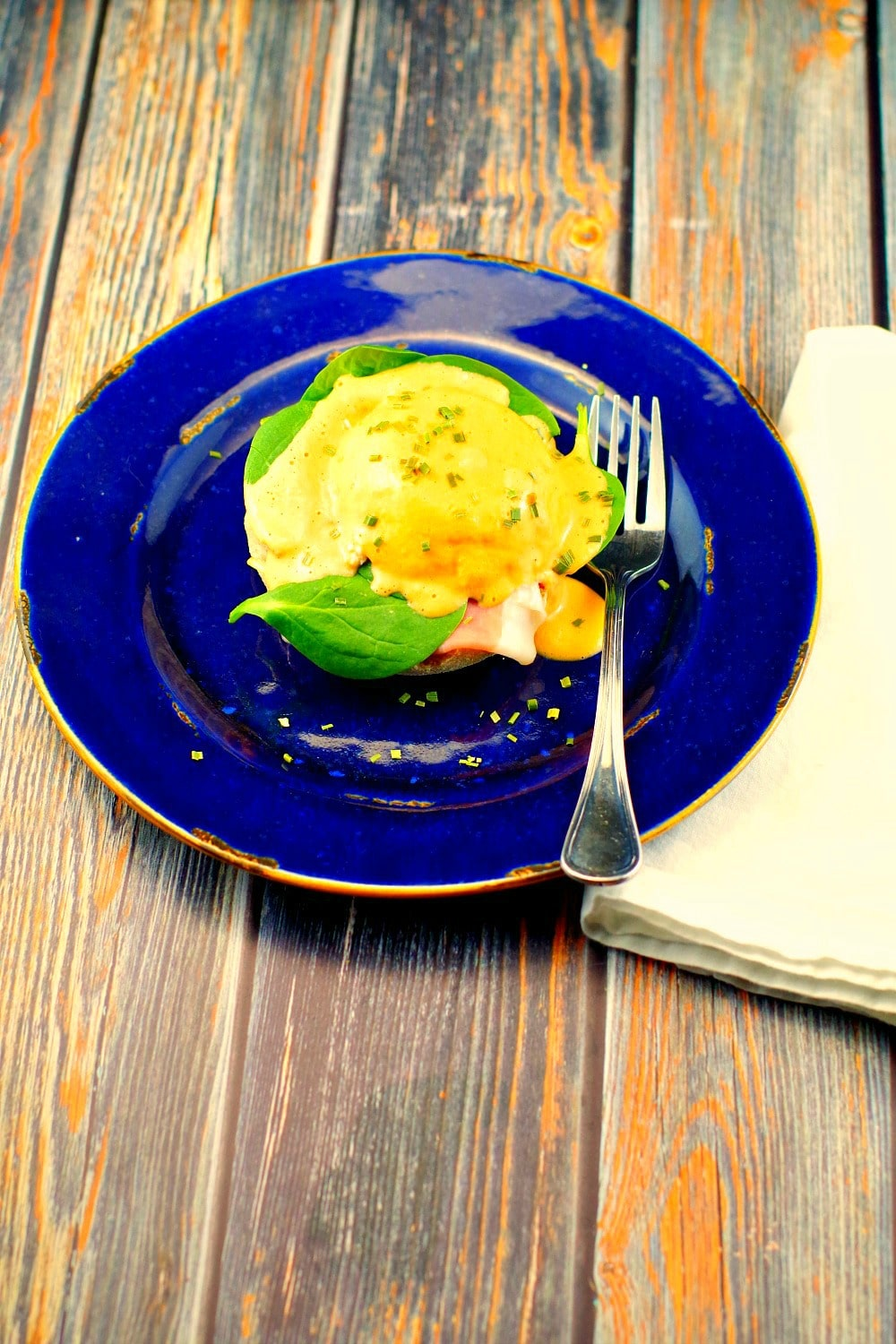 eggs benedict on a blue plate on wooden surface
