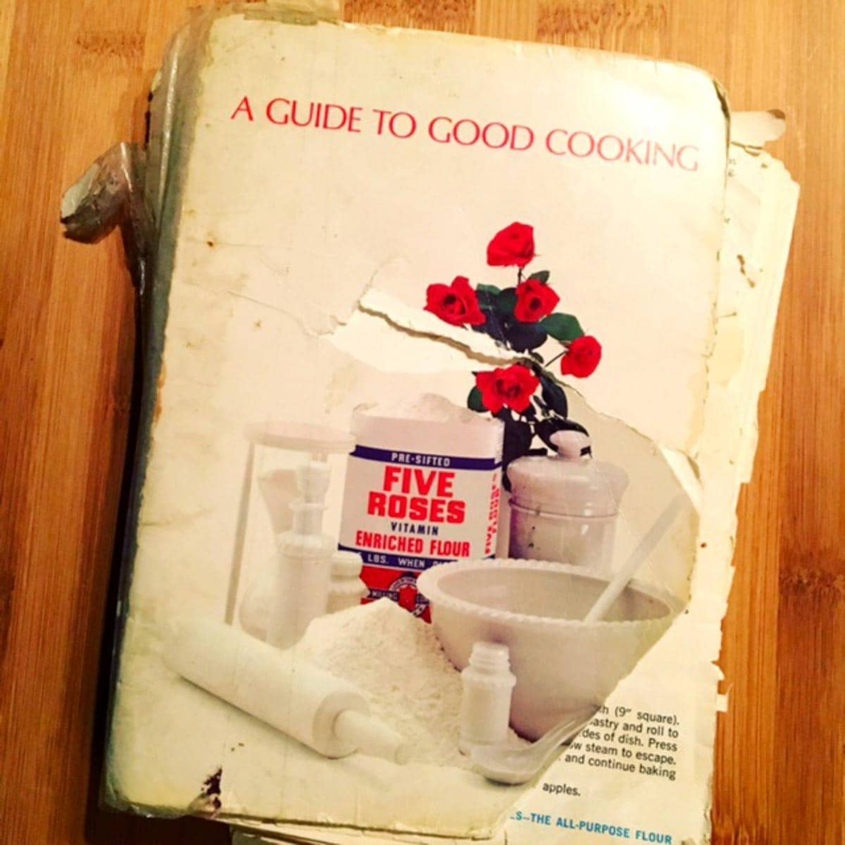 a worn out copy of the Five Roses Cookbook sitting on a table