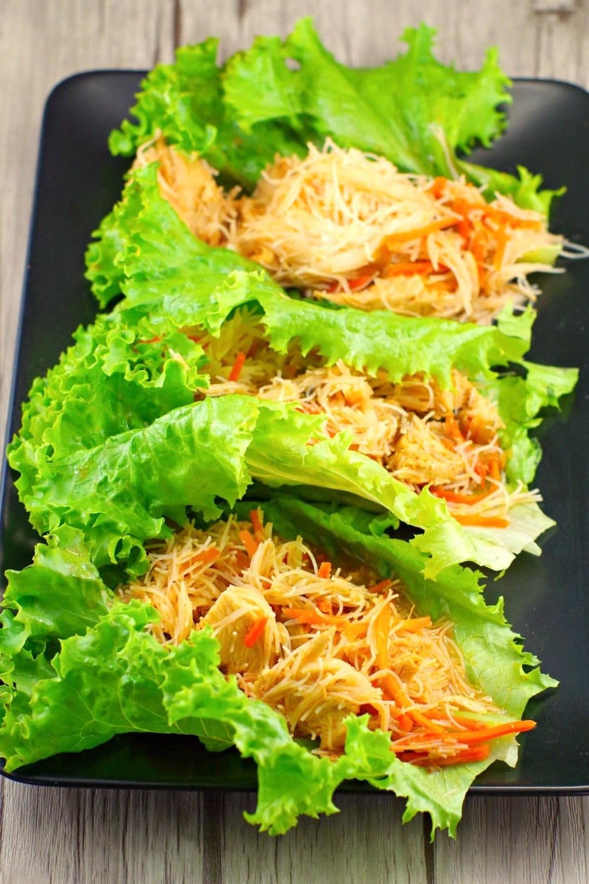 3 honey sriracha chicken lettuce wraps on a black platter
