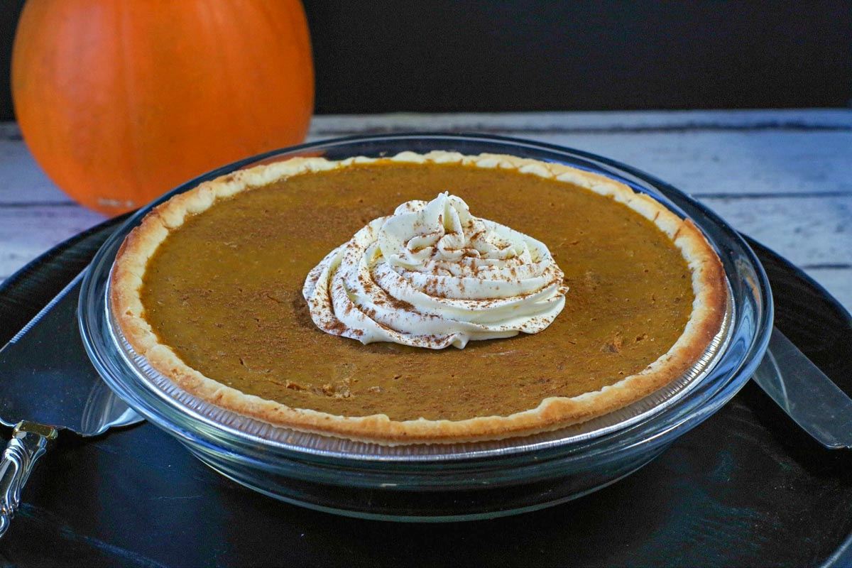 Whole pumpkin pie with pumpkin in the background, with whipped cream in the middle