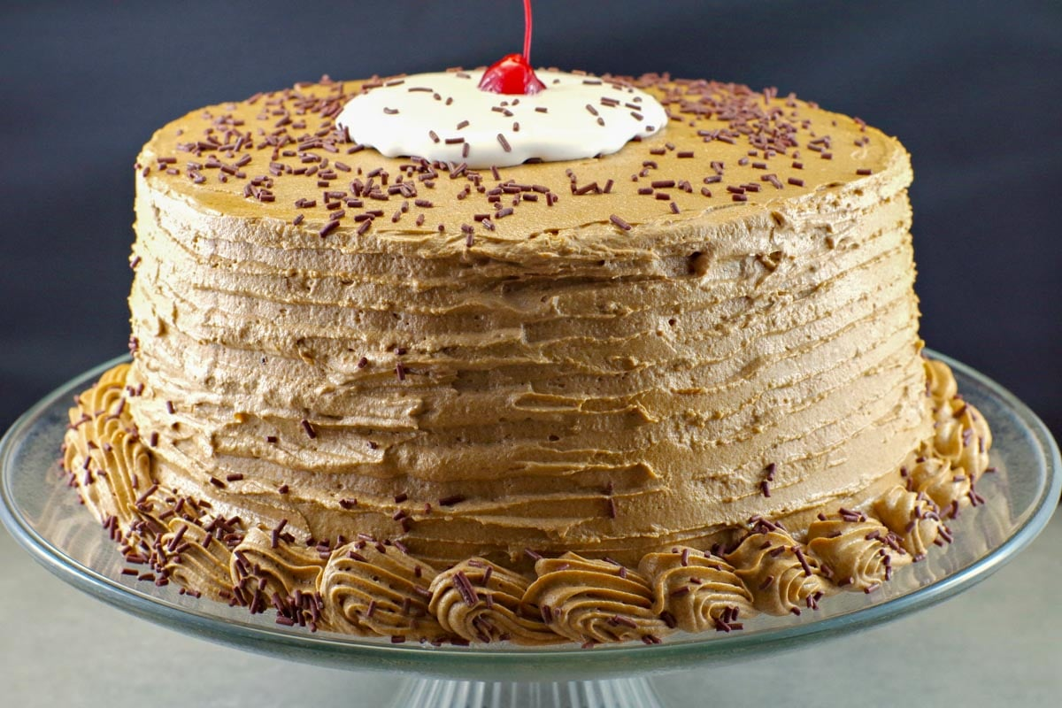 whole root beer float cake on a clear glass cake platter with black background