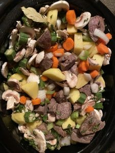 meat, veggies an herbs in a slow cooker
