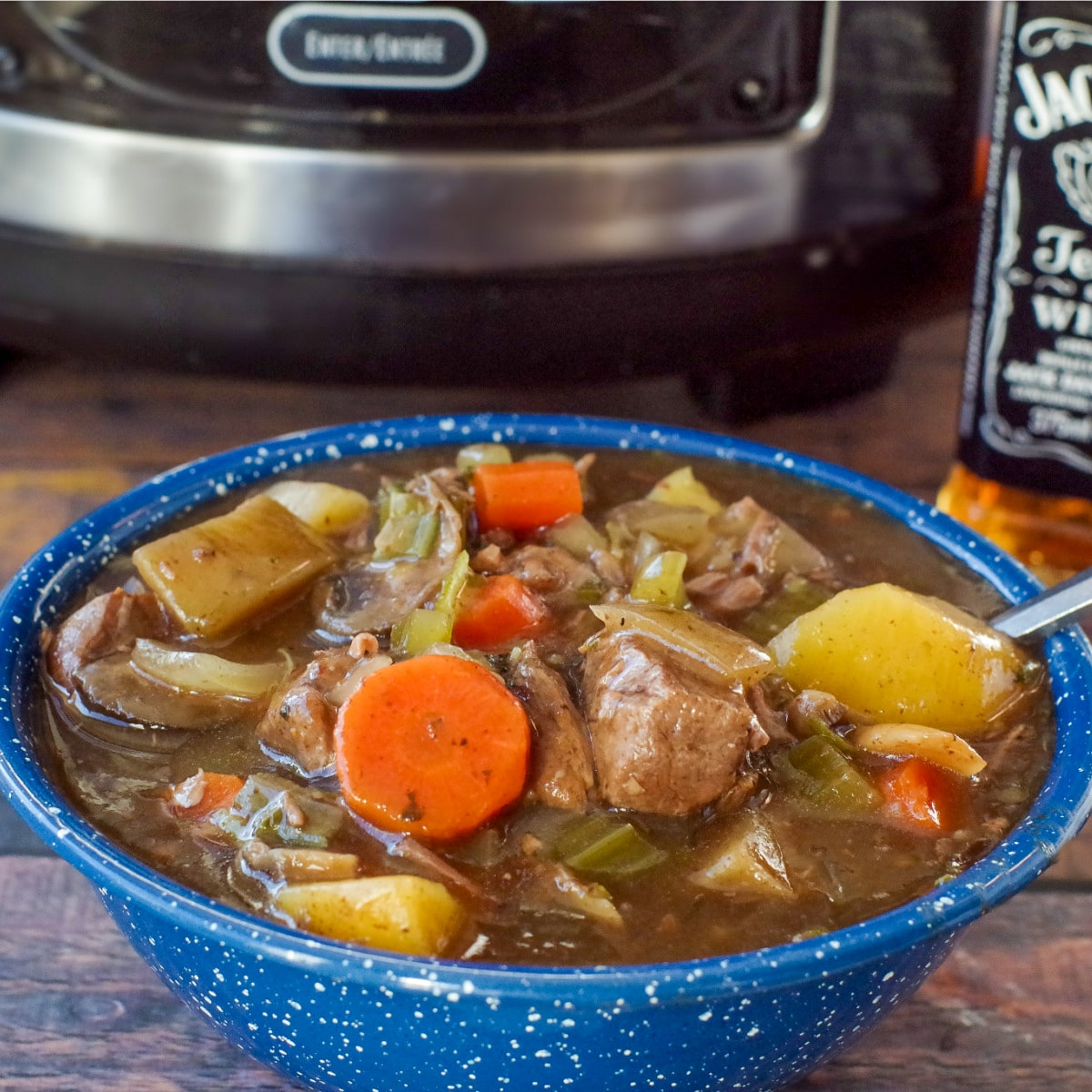 slow cooker beef stew in a blue bowl with slow cooker in the background