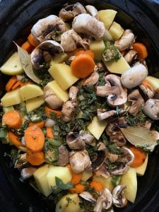 meat, veggies and herbs with liquid poured over, in slow cooker