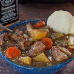 slow cooker beef stew in a blue bowl with a biscuit and slow cooker and bottle of whiskey in the background
