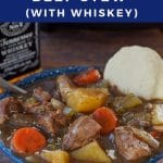 pin with white text on blue background on top and bottom and photo of slow cooker beef stew in a blue bowl with a biscuit and slow cooker and bottle of whiskey in the background
