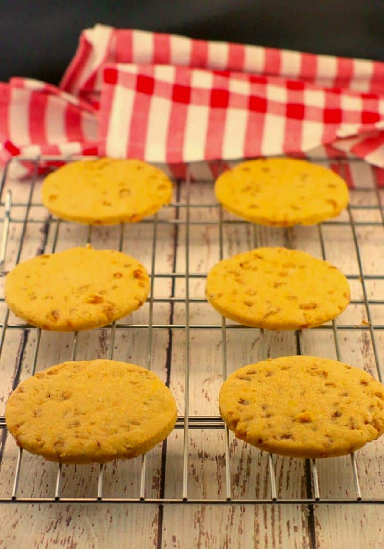 butterscotch toffee cookies on a wire cooling rack, with checkered red and white tablecloth