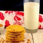 stack of butterscotch toffee cookies with a glass of milk and red and white tea towel in the background