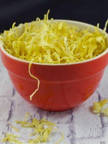 parsnip crisps/fried parsnips in an orange bowl on white surface
