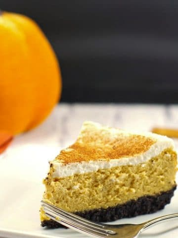 low-fat pumpkin cheesecake on a white plate with a stuffed pumpkin in the background