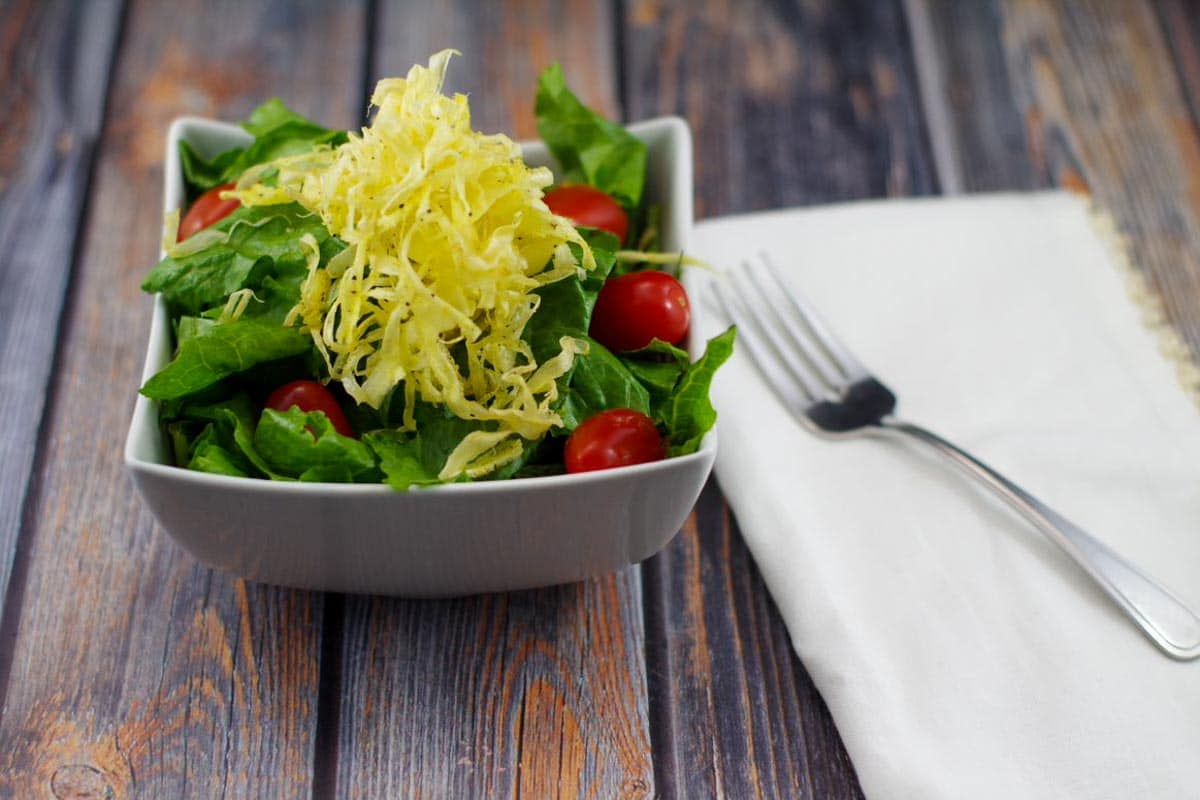 parsnips chips on top of salad in a white bowl