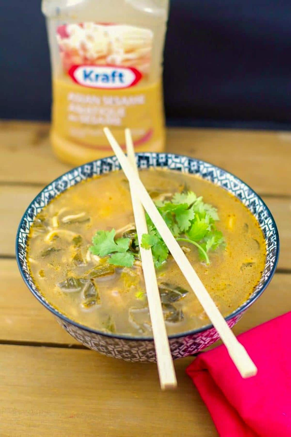 Quick Asian beef soup in a checkered bowl with chopsticks on top of the bowl and a bottle of Asian Sesame salad dressing in the background