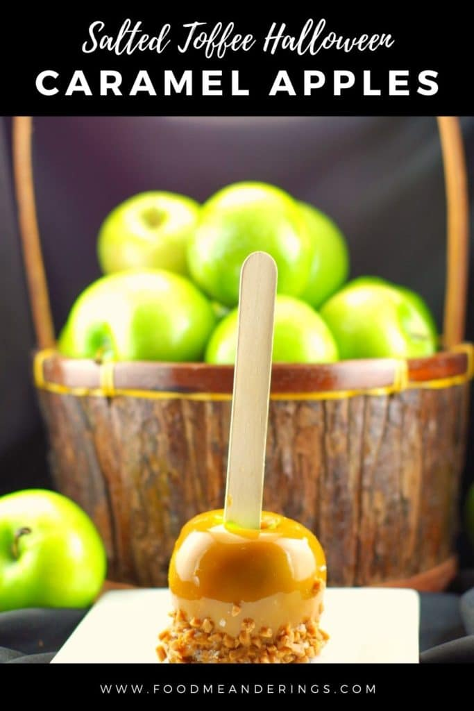 salted toffee halloween caramel apple on a white plate in front of a basket of green apples
