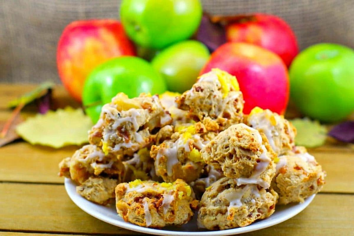 Toffee Apple Pie Cookies on a white plate, with apples in the background
