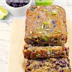 Blueberry Gingerbread Loaf on cutting board with blueberries and lime in background