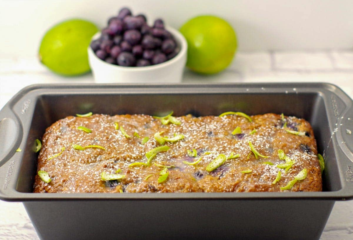 blueberry gingerbread loaf in a pan with blueberries and limes in the background