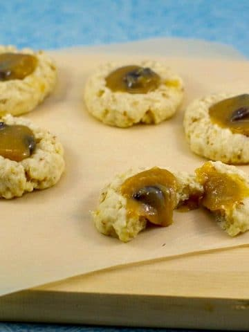 butter tart cookies on a piece of parchment paper (on cutting board) with 1 cookie split in half