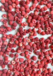 Frozen raspberries on parchment lined cookie sheet