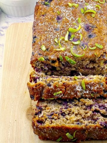 gingerbread loaf on a cutting board with blueberries and limes in background