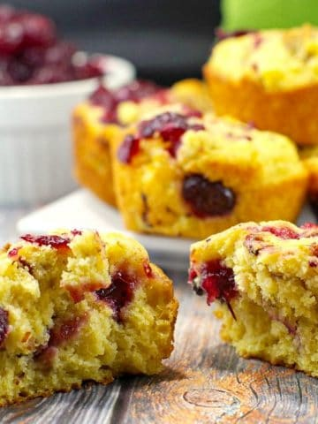 cranberry cornbread muffin split in half, with more cranberry cornbread muffins on a white plate, and a dish of cranberry sauce, in the background