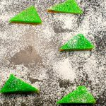 lime squares with powdered sugar on a cutting board with powdered sugar and space where one has been removed