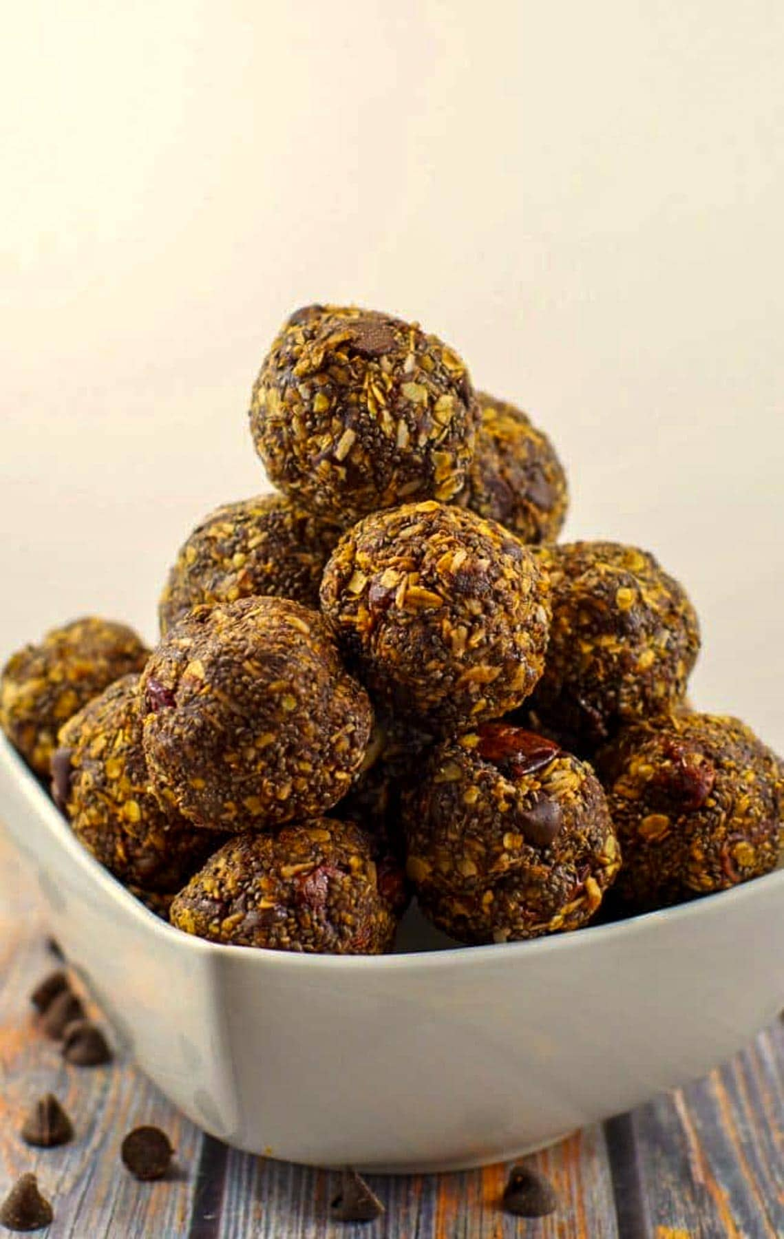 chocolate cherry energy balls stacked in a white bowl