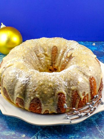 whole butter tart cake on a white plate with gold Christmas ornaments in background