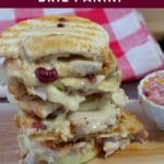 Pinterest pin with white text on cranberry colored background on top and bottom and photo of leftover turkey sandwich on a cutting board with checkered towel in background in the middle