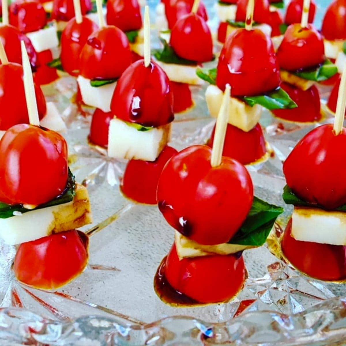 caprese salad skewers on sticks on crystal platter