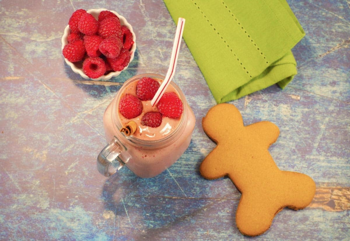gingerbread raspberry smoothie shot from above with gingerbread man and bowl of raspberries on either side of smoothie