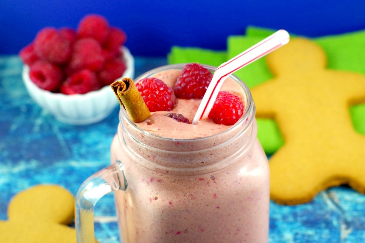 raspberry gingerbread smoothie with a bowl of raspberries and a gingerbread man in the background